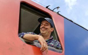 Railmen-Lokführer Steffen Mann mit Basecap und Schnautzer blickt aus dem Seitenfenster eines Güterzuges.