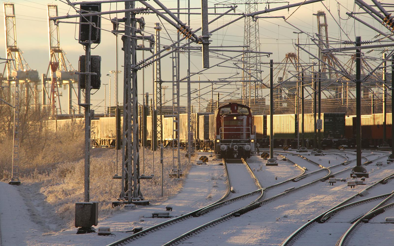 Foto: railmen-Lokführer Denis Herwig ist als Lokführer insbesondere für Güterverkehre überall in Deutschland unterwegs. Hier fotografierte er den Sonnenuntergang in Bremerhaven, Bahnhofsteil Weddewarder Tief, die BR 294 mit Containerzug im Januarschnee 2016.