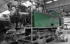 Frau führt letzte Handgriffe an einer fast fertig aufgearbeiteten Schmalspur-Lokomotive aus