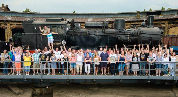 Große Gruppe von Lokführern stehen winkend mit Ihren Partnern und Familie aufgereiht vor einer alten Dampflok