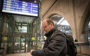 Railmen-Lokführer Jan Krehl steht in der Ankunftshalle des HBF Leipzig und prüft die Pünktlichkeit der MRB.