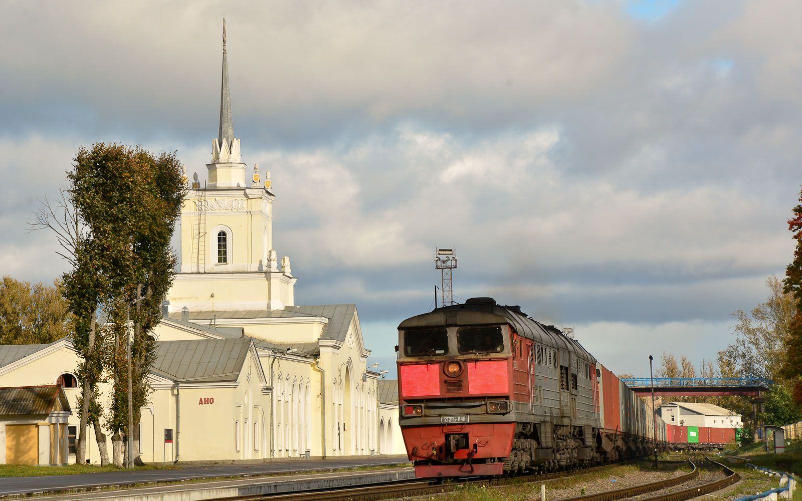 ©Foto: railmen Steffen Mann | 2TE116-648 mit Güterzug durchfährt Bahnhof Dno | Das helle Bahnhofsgebäude besticht durch seinen Spitzturm | 25.09.2018