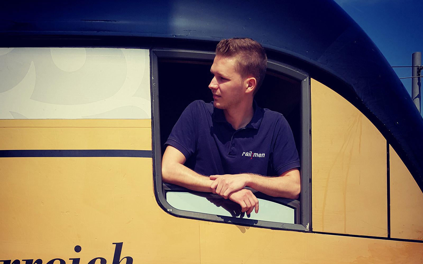 railmen Lokführer schaut aus dem Seitenfenster des Triebwagens