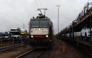 Gleise mit mehreren Autozügen in der Frontalansicht fährt gerade ein Lok der Baureihe 185 vor