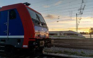 ICE mit grüner Bauchbinde überholt Güterzug bei Augsburg