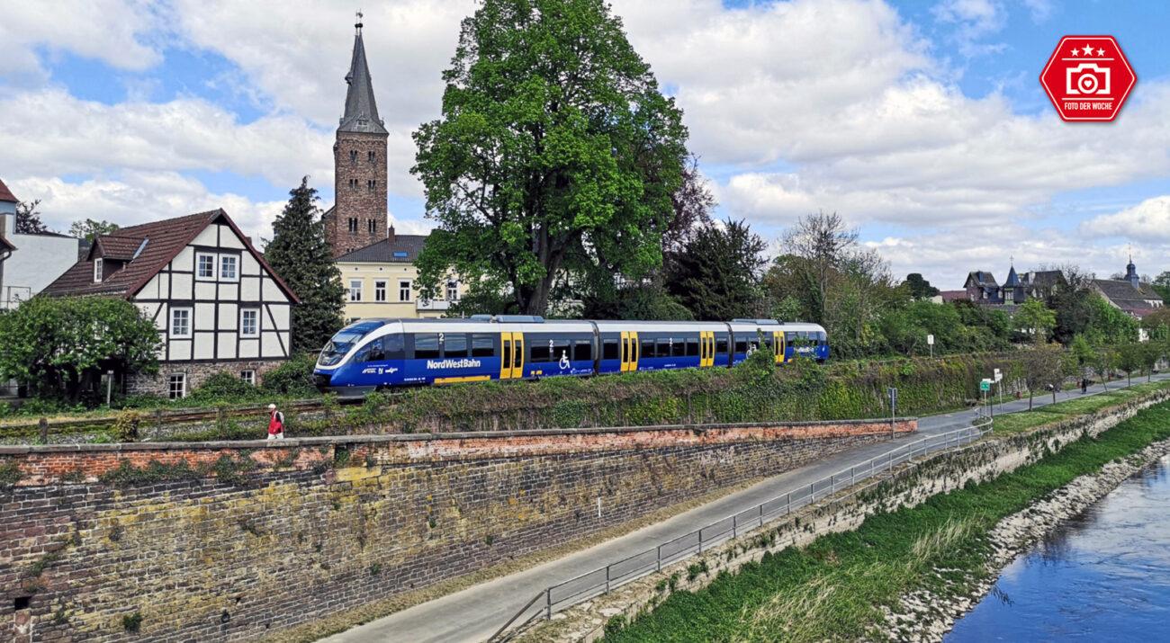 Nordwestbahn (NWB) in Höxter. Im Vordergrund ist die Weser zu sehen und der Zug befindet sich auf dem Weg von Holzminden nach Paderborn.